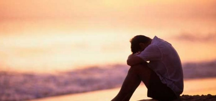 homem frente ao mar depressivo e com sofrimento