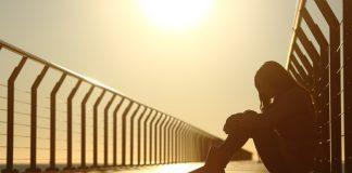 mulher sentada pensando na tristeza